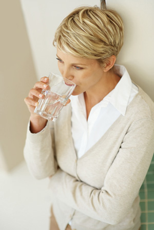 A blonde woman stays hydrated by drinking from a glass of water