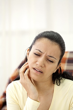 A brunette woman in pain massaging her sore jaw