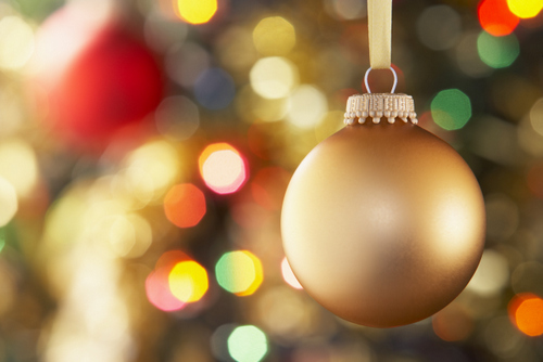 Close up of a pretty, gold ball ornament hanging in a holiday tree