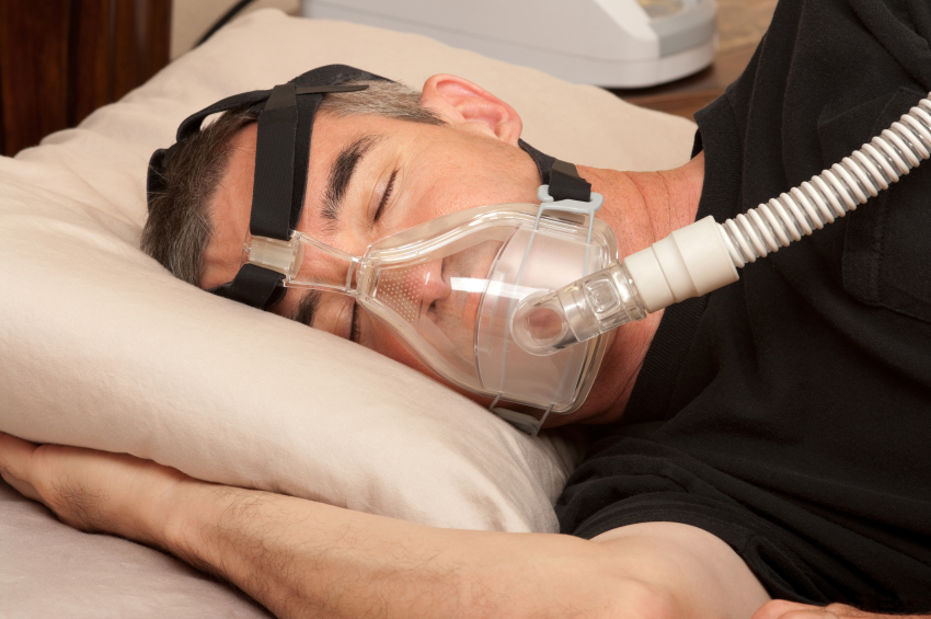 A man sleeps in bed wearing a full-face CPAP machine to treat his obstructive sleep apnea