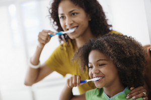 A mother teaching her daughter how to properly brush her teeth