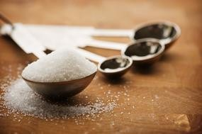 Close up of a tablespoon filled with sugar resting on a wooden countertop